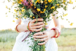 A hippy girl holding a bouquet of wildflowers in her hands