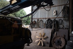 A huge metallic fan of a heavy machinery in the middle. A big gear and car tires on the right. Rusty. Silhouette of a machinery and other truck parts around.