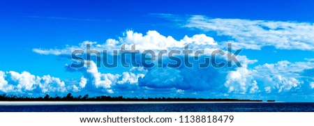 A Huge tropical atmospheric cloudy sky cloudscape with white coloured Cumulonimbus cloud formation in a blue sky. Beauty in nature. Fraser Island, Australia.