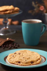 A large and delicious chocolate chip cookie accompanied by a cup of coffee on a rustic background.