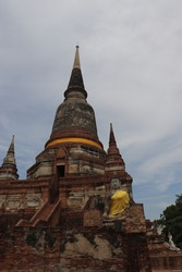 A large and tall pagoda constructed from ancient bricks, with a Buddha statue in the front, it is Thai art, a highly popular tourist destination. In Ayutthaya province, Thailand