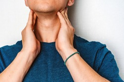 A man checks the lymph nodes on his neck.