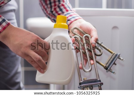a man holds in his hand the heating elements of the washing machine and the descaling agent or detergent