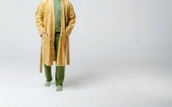a man in a dressing gown, without a face in the studio on a white background in a green T-shirt, pants, socks