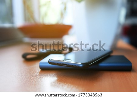 a man playing with smartphone While charging the smartphone battery and device Charge Sharing. martphone charging with white power bank. close-up at white power bank.
