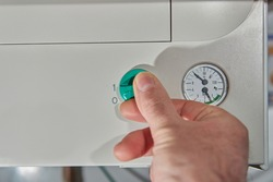 A man's hand activating the control of a natural gas boiler