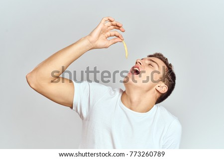 a man with an open mouth holding a potato on a light background                               #773260789