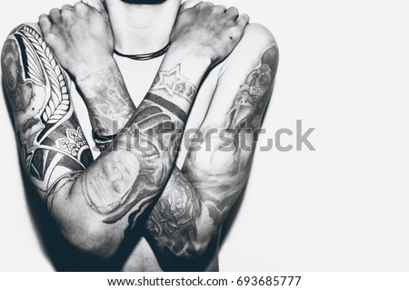A man without a shirt, with his hands full of tattoos.  #693685777