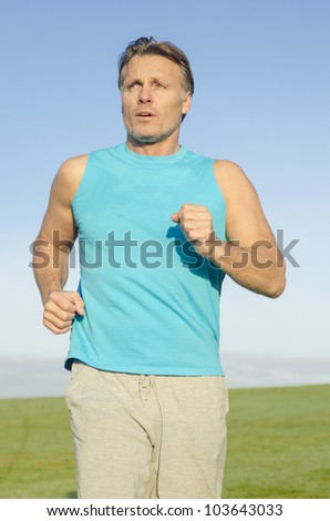 A mature forties man jogging in blue shirt