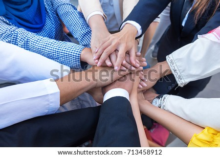 A meeting of Arab and Asian employees to work together as a team for success. The hand of the group represents the teamwork. It makes people in the company confident and work happily. #713458912