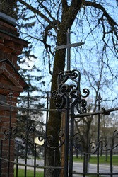 a metal gate with a cross in the cemetery of the Catholic Church