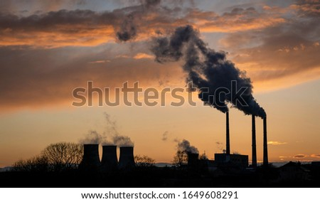 A metaphor of human exposure to nature, carbon emissions. Industrial landscape: smoke from the pipes of a thermal power plant at sunset.