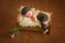 A newborn in a fashionable suit sleeps in a crib. Photoshoot of a newborn. Stylish suit for the baby. Fashion kid. A newborn in a cap and hats. The child sleeps in the crib. Deep sleep