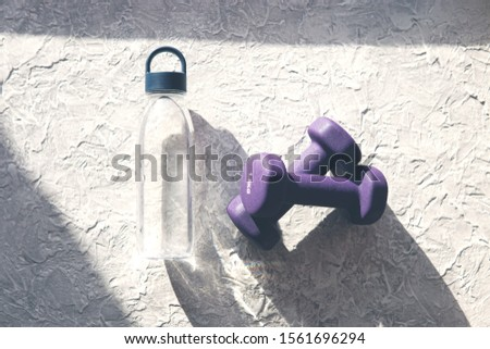 A pair of purple 1.5 kg dumbbells and a bottle of water on textured grey background with sunny light and shadows. Top view, flat lay. Healthy life, fitness concept.