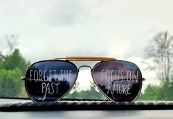 A pair of sunglasses on the car dashboard with a beautiful scenery background with written text forget the past, focus on future. Selective focus.