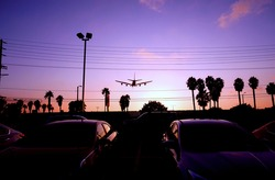 A passenger plane heading to Los Angeles Airport during the beautiful magic hour of the sunset in the United States