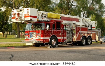 A picture of a fire truck on a residential street in the late evening sun