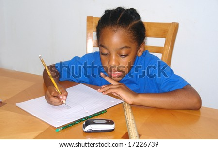 A picture of a young boy studying at table