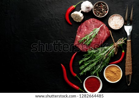 a piece of meat from the butcher shop, one piece of beef in the form of a steak on a dark concrete background with ingredients