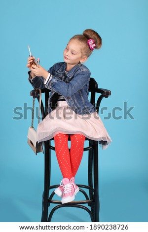 A pin-up girl in pink sneakers with untied laces, red tights, a chiffon skirt and a denim jacket, sits on a high chair with a handbag on a blue background and paints her lips with lipstick. Stock photo ©