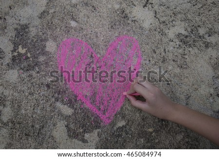 A pink heart symbol is drawn on a sidewalk outside with chalk #465084974