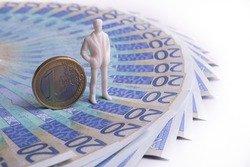 A plastic figurine of a symbolic person stands next to a 1 euro coin against the background of 20 euro bills on a white background