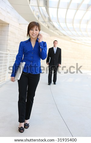 A pretty asian business woman on at company with co-worker in background