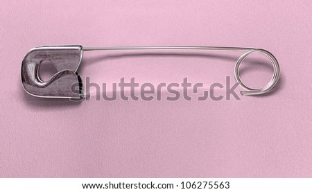 A regular baby safety pin fastened to a pink fabric