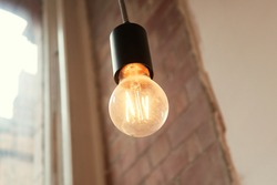 A retro vintage style victorian filament right bulb in a trendy downtown city interior environment. Fashionable addison orange light coffee shop hipster lighting. steampunk inspires lights.