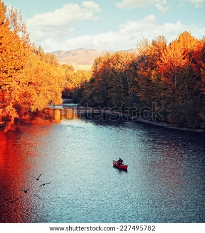a river flowing in autumn with a kayaker paddling in the water #227495782
