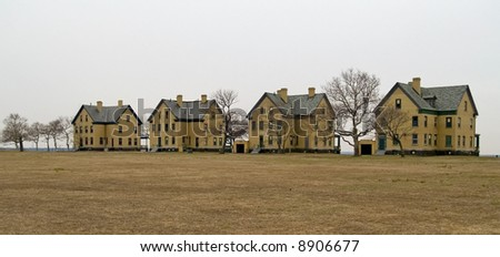 A row of turn of the 20th century yellow brick homes was part of the Barracks of Fort Hancock on Sandy Hook, along the Jersey shore. - stock photo