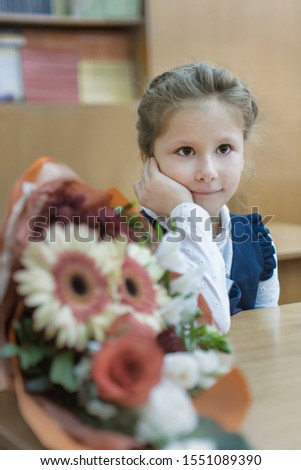 A schoolgirl of primary classes sits at a desk and listens to a lesson. Day of knowledge. First of September. The beginning of the school year. Concept of education.
