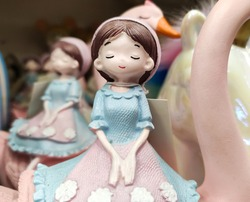 A sculpture of a girl in a blue dress and a pink ceramic apron against a background of a goose. A small figurine of a girl - decor for the holiday.