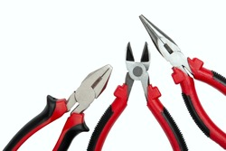 a set of three different hand tools: pliers, side cutters, long nose pliers on a white isolated background close up