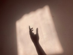 a shadow of the hand that is on the pink wall in the morning