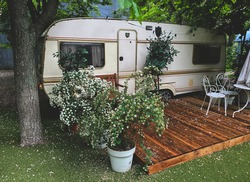 a small cozy trailer in summer camping with a French-style courtyard among the park or forest, trailer , summer camp, traveling