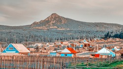 A small Ural village on the background of a high mountain arvyakryaz in the Southern Urals in Bashkortostan.