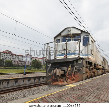 A speeding diesel powered train zooming through a rural outdoor train station.