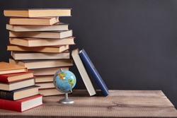 a stack of books and globe on the table in the classroom.