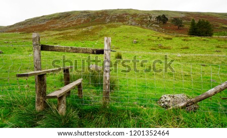 A stile leading to a meadow and hills                         - Shutterstock ID 1201352464