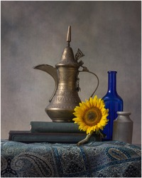 A still life of an Arabian Coffee Pot, Sunflower and antique items inspired by old master paintings.