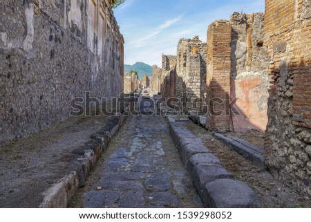 A street in the ancient city of Pompeii, Italy. In the background you can see the volcano Vesuvius.