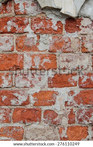 a thick layer of plaster on the surface of a wall of red brick, texture