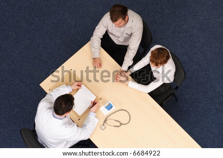 A top view of a couple sitting opposite a doctor at his table during a medical consultation. doctor talking about medical record