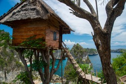 A tree house with a thatched roof and a wooden staircase in the background of a turquoise bay and high cliff from the Thousand Islands Viewpoint. In the foreground is the trunk of another tree.