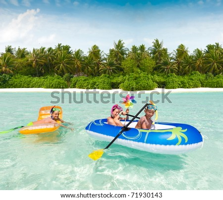 A trio of kids playing in a raft at the beach.