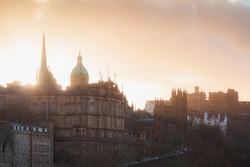 A view of Museum on the Mound, Ramsay Garden, Edinburgh Castle and Old Town Edinburgh cityscape skyline at sunset or sunrise from Waverley Station.