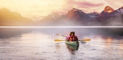 A wanderlust couple explore in a canoe on a lake in beautiful serene, tranquil, panoramic mountain backdrop, seeking adventure