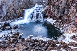 A waterfall in Iceland cascades down the side of a rugged mountain into a natural pool