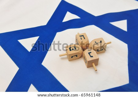 A white and blue Israeli Flag with the star of David on it with wooden dreidels for the Jewish holiday of Hanukkah.